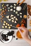 Cheese and fruit mix on the black stone with woman hand Stock Photography