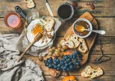 Cheese, fruit, nut and wine set over rustic wooden background Royalty Free Stock Images