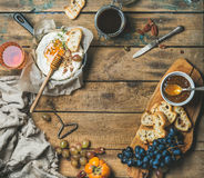 Cheese, fruit, nut and wine set over rustic wooden background Stock Photography