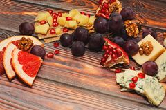 Cheese and fruit snack. Aged gourmet cheese and fresh fruits platter. Light and gourmet delicious snack in european way, ideal with red wine. Close-up capture Royalty Free Stock Image