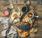 Cheese, fruit and wine set over rustic wooden background Royalty Free Stock Images