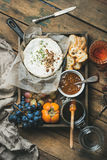Cheese, fruit, wine set in wooden tray over rustic background Royalty Free Stock Photos