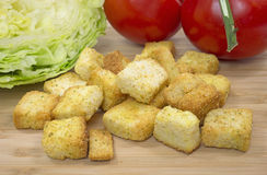 Cheese and garlic croutons on cutting board Stock Photography