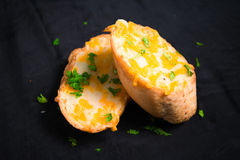 Cheese garlic and herb bread slices on black background Stock Photo