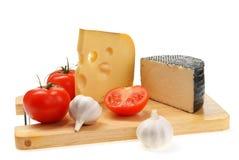 Cheese, garlic, tomato on a board Royalty Free Stock Photo