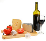 Cheese, garlic, tomato on a board Stock Photos