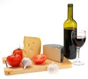 Cheese, garlic, tomato on a board Stock Photos