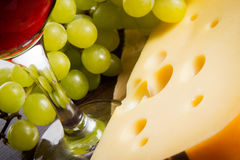 Cheese, a glass of red wine in the glass and a handful of grapes. Food closeup background. Cheese, a glass of red wine in the glass and a handful of grapes stock photo