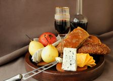 Cheese, a glass of wine, fruit and bread. Stock Photos