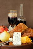 Cheese, a glass of wine, fruit and bread. Stock Photo