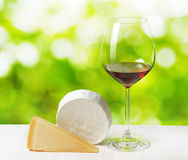 Cheese and glass of wine on nature background royalty free stock image