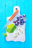 Cheese. With grape on the board Royalty Free Stock Photos