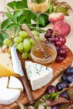 Cheese, grape and wine glass. Cheese with grapes, honey and wine glass on wooden background stock images