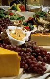 Cheese and grapes. Cheese, grapes, crackers, vegetables on a table Stock Image