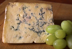 Cheese & Grapes. Green grapes with stilton cheese on a board Stock Images