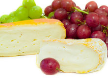 Cheese and grapes. Cheeses with green and red grapes on a white background Stock Photography