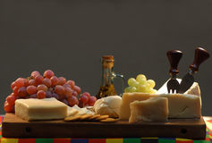 Cheese and grapes. Cheese and grapes under bright light on a dark background royalty free illustration
