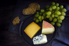 Cheese, grapes and bread on a dark rustic wooden table, view fro Stock Photography