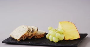 Cheese, grapes and bread on tray. Against white background stock video footage