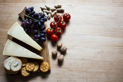 Cheese with grapes and cherry tomatoes, cracker, nuts, fruits and nuts. View from above. Cheese on a visible background. Copy stock photo