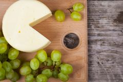 Cheese and grapes on a cutting board Royalty Free Stock Photos