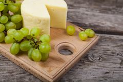 Cheese and grapes on a cutting board Royalty Free Stock Images