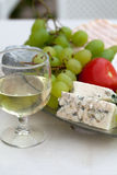 Cheese, grapes and glass of the white wine Stock Images