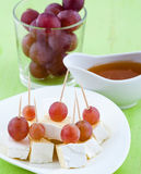 Cheese, grapes and honey. Cheese Served with grapes and honey on a plate Royalty Free Stock Images