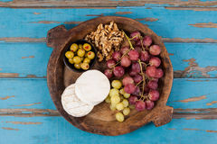 Cheese, grapes, olives and walnuts in wooden bowl Royalty Free Stock Photo