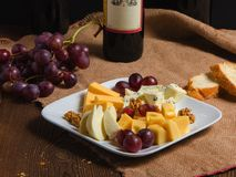 Cheese and grapes on a plate stock image