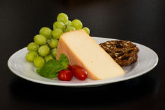 Cheese and grapes on plate Royalty Free Stock Image