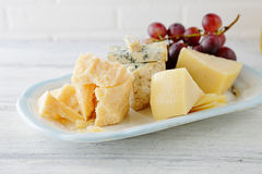 Cheese and grapes on plate Royalty Free Stock Photo