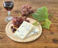 Cheese, grapes and wine on wood Stock Images