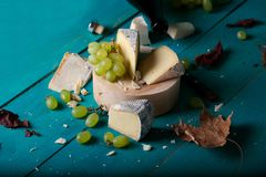 Cheese, grapes and wine on wooden cyan surface. royalty free stock photos