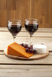 Cheese grapes and wineglass Stock Photos
