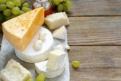 Cheese with grapes on wooden background Royalty Free Stock Images