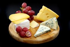 Cheese and grapes on a wooden board. royalty free stock image