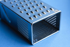 Cheese-grater. Detail of a stainless steel cheese-grater against a blue background Royalty Free Stock Images
