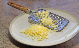 Cheese grater and cheese on a dish. Stock Photos