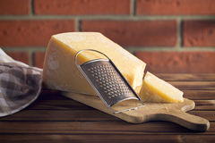 Cheese grater and parmesan. The cheese grater and parmesan stock photos