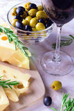 Cheese with green and black olives and glass of red wine Royalty Free Stock Image
