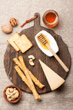 Cheese,  grissini bread sticks, honey and nuts Royalty Free Stock Photo