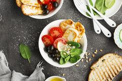 Cheese haloumi brown rice bowl with tomatoes, olives, lemon and pine nuts. Top View.  Royalty Free Stock Images