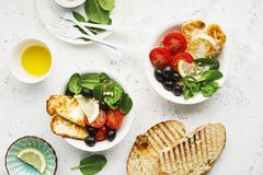 Cheese haloumi brown rice bowl with tomatoes, olives, lemon and pine nuts. Top View.  Royalty Free Stock Image