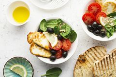 Cheese haloumi brown rice bowl with tomatoes, olives, lemon and pine nuts. Top View.  Stock Images