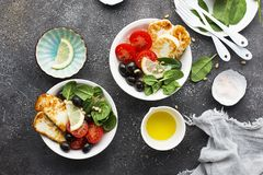 Cheese haloumi brown rice bowl with tomatoes, olives, lemon and pine nuts. Top View.  Royalty Free Stock Photography