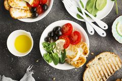 Cheese haloumi brown rice bowl with tomatoes, olives, lemon and pine nuts. Top View.  Royalty Free Stock Photos