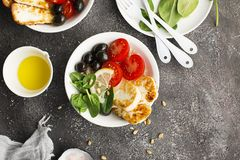 Cheese haloumi brown rice bowl with tomatoes, olives, lemon and pine nuts. Top View.  Stock Image