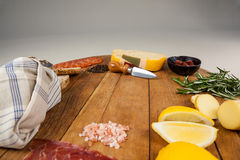 Cheese, ham and bread with various ingredients on chopping board. Against white background Stock Images