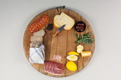 Cheese, ham and bread with various ingredients on chopping board. Against white background Stock Photos
